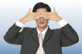 businessman with his hands over his eyes
